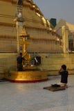 Los budistas ruegan en los posts planetarios Foto de archivo libre de regalías