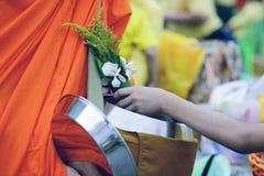 Los budistas traen la comida y las flores a los monjes para hacer el m?rito para los monjes seg?n creencias budistas imagenes de archivo