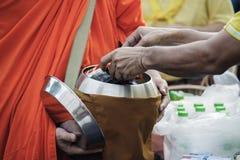 Los budistas traen la comida y las flores a los monjes para hacer el m?rito para los monjes seg?n creencias budistas imagen de archivo libre de regalías