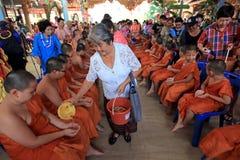 Los budistas vierten el agua en novatos imagenes de archivo