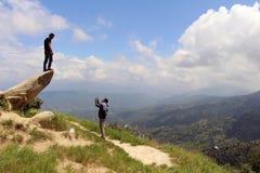 Los buenos amigos Nepali están ayudando a tomar las fotos en una piedra imagen de archivo