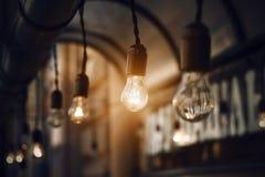 Los bulbos brillan intensamente brillantemente en la oscuridad de la noche imagenes de archivo
