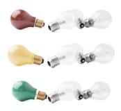 Los bulbos coloreados que mentían al lado de los pares de bulbos transparentes sobre blanco aislaron el fondo fotos de archivo libres de regalías
