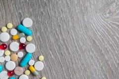 Los bunte Medikation und Pillen von oben genanntem auf grauem hölzernem Hintergrund Kopieren Sie Platz Draufsicht, Rahmen Schmerz stockbild