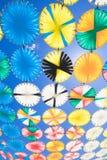 Los círculos multicolores de la sombrilla reman en vertical del cielo azul fotos de archivo