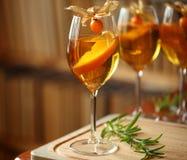 Los cócteles en las copas, adornadas con la naranja y el physalis en tabla de cortar de madera con romero cerca, reservan en el f Fotos de archivo