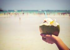 Los cócteles frescos del coco con en las manos de la mujer en la playa tropical - vacation en verano Fotografía de archivo