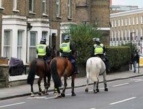 Los caballos montados por los oficiales de la policía metropolitana montaron la rama que ejercitaba los animales en el camino cru imágenes de archivo libres de regalías