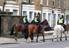 Los caballos montados por los oficiales de la policía metropolitana montaron la rama que salía de establos a ejercitar los animal imágenes de archivo libres de regalías