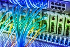 Los cables de fribra óptica y la red de UTP telegrafía puertos conectados del eje Imágenes de archivo libres de regalías