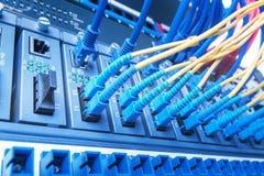 Los cables de fribra óptica y la red de UTP telegrafía puertos conectados del eje Fotos de archivo libres de regalías