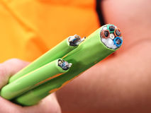 Los cables de fribra óptica vestidos de nylon verdes lían de mano Imagenes de archivo