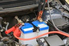 Los cables de puente de la batería de las aplicaciones de mecánico de coche cargan una batería muerta fotografía de archivo