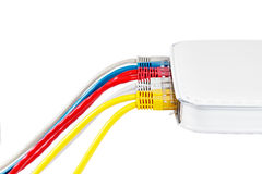 Los cables multicolores de la red conectaron con el router en un fondo blanco Imagen de archivo