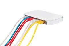 Los cables multicolores de la red conectaron con el router en un fondo blanco Fotografía de archivo