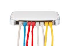 Los cables multicolores de la red conectaron con el router en un fondo blanco Foto de archivo libre de regalías