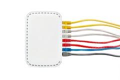 Los cables multicolores de la red conectaron con el router en un fondo blanco Imagen de archivo libre de regalías