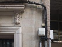 Los cables sucios del teléfono o de la electricidad colgaron en una pared de piedra foto de archivo libre de regalías