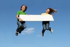 Los cabritos que saltan con la muestra en blanco Foto de archivo libre de regalías