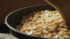 Los cacahuetes pelados se fríen en una cacerola Mano con una cuchara que revuelve nueces almacen de metraje de vídeo