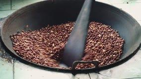 Los cacahuetes pelados son cacerola grande de Fried In A Mano con una cuchara que revuelve nueces almacen de video
