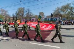 Los cadetes del club patriótico van en desfile con la bandera Foto de archivo libre de regalías