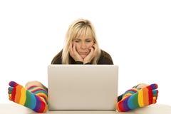 Los calcetines coloreados mujer se sientan por las manos del ordenador en cara Imagenes de archivo