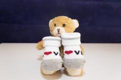 Los calcetines rojos y blancos del bebé - con refieren el fondo blanco Fotos de archivo
