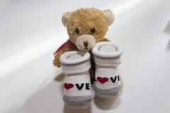 Los calcetines rojos y blancos del bebé - con refieren el fondo blanco Foto de archivo libre de regalías