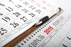 Los calendarios de pared con la pluma pusieron en la tabla Fotografía de archivo libre de regalías