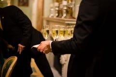 los camareros en librea sirven los vidrios de vino blanco chispeante, Fotos de archivo libres de regalías
