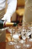Los camareros en los guantes blancos vertieron el champán Imágenes de archivo libres de regalías