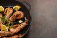 Los camarones de las gambas con ajo, el limón, las especias y el perejil italiano adornan en una cacerola negra en la madera rúst imagen de archivo