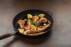 Los camarones de las gambas con ajo, el limón, las especias y el perejil italiano adornan en una cacerola negra en un fondo de pi Fotografía de archivo libre de regalías