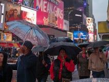 Los caminante sostienen los paraguas que ven las señales de neón del Times Square encendido fotografía de archivo libre de regalías