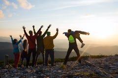 Los caminantes alegres, amigos con los brazos abiertos se están colocando en un top Imagen de archivo libre de regalías