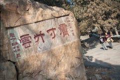 Los caminantes caminan más allá de una roca grande con la inscripción china en Tai Shan, China Imagen de archivo