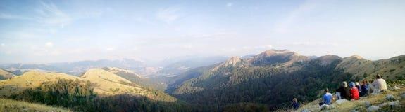 Los caminantes de la montaña fijaron en una cumbre para admirar el paisaje y el wildli Foto de archivo libre de regalías