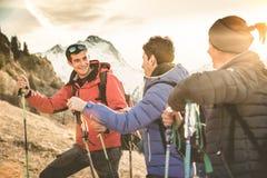 Los caminantes de los amigos agrupan el senderismo en la montaña francesa de las montañas en la puesta del sol Foto de archivo libre de regalías