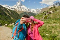 Los caminantes de un par que caminan con las mochilas caminan a lo largo de un área de montaña hermosa Fotografía de archivo