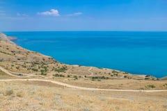 Los caminos y el mar ajardinan en el cabo Meganom, la costa este de la península de Crimea Fondo colorido, concepto que viaja foto de archivo