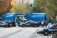 Los camiones de la policía y de basura previenen actos posibles del terrorismo en el desfile Foto de archivo libre de regalías
