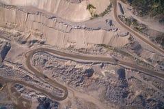 Los camiones industriales se mueven a lo largo del camino en la mina de la arena Fotos de archivo libres de regalías