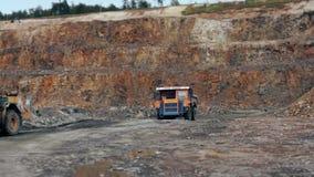 Los camiones pesados llevan la piedra fuera del granito de la explotación minera de la mina almacen de video