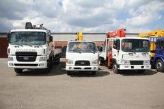 Los camiones planos blancos con el brazo de las grúas están en el estacionamiento - Rusia, Moscú, el 30 de agosto de 2016 Fotos de archivo