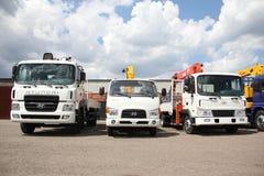 Los camiones planos blancos con el brazo de las grúas están en el estacionamiento - Rusia, Moscú, el 30 de agosto de 2016 Fotografía de archivo libre de regalías