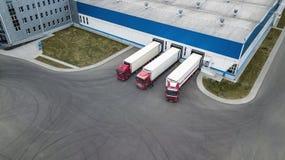 Los camiones se cargan en un centro moderno de la logística foto de archivo
