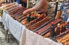 Los campesinos armenios venden los dulces hechos a mano sabrosos de la fruta en el mercado al aire libre imagenes de archivo