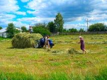 Los campesinos cargan el heno en el pueblo imagen de archivo libre de regalías