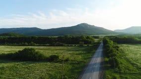 Los campos de hierba verde ajardinan con las montañas fantásticas en el fondo tiro Asfalto la carretera con los prados verdes, ar metrajes